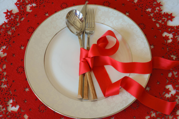 Top view on Christmas And New Year Holiday Table Place Setting with cutlery. Flat lay, red woolen and white background. Winter holidays concept