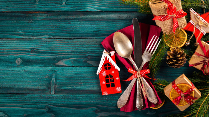 Christmas serving cutlery with plate on a wooden background.