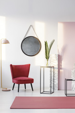 Round mirror hanging on white wall in room interior with burgundy velvet chair, red carpet and fresh leaves in glass vase