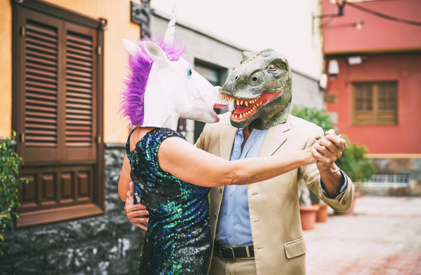 Crazy couple dancing and wearing dinosaur t-rex and unicorn mask - Senior elegant people having fun masked at carnival parade - Absurd, eccentric, surreal, fest and funny masquerade concept