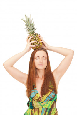 Girl with pineapple is pretending it is a crown