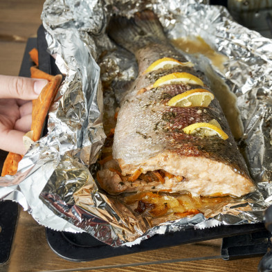 Trout fish freshly baked in a foil with lemon slices and vegetables in an electric oven